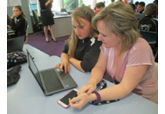 A parent assisting their child with their Pathways Plan on a laptop in the classroom