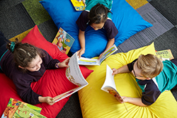 Photo of three primary school students, two girls and a boy, lying on colourful cushions, each reading a picture book, surrounded by other books on the floor