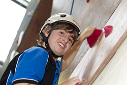 Photo of a boy student climbing an indoor 'rock wall' in an outdoor education class at Gungahlin College