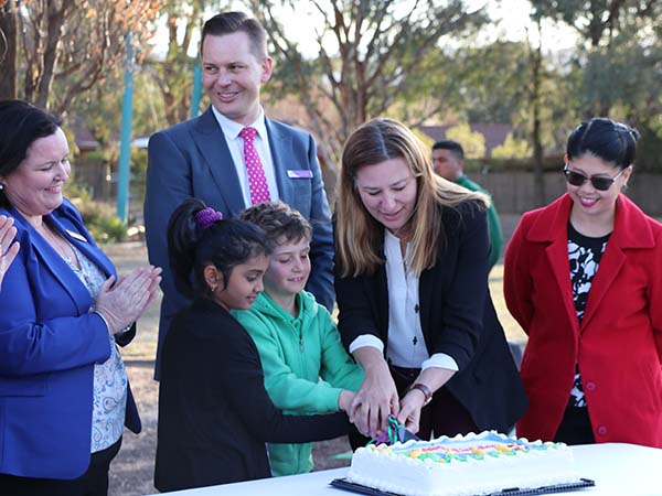 Hosts Max and Simrah cutting the cake with ACT Education Minister, Yvette Berry