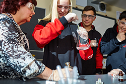 Photo of a female teacher assisting a female high school student to conduct a chemistry experiment, wearing protective gloves and goggles and using a pipette and beaker, while two male students look on