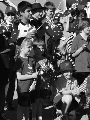 Photo of primary aged students welcoming Queen Elizabeth II of Australia, with a smile and waving Australian flags.