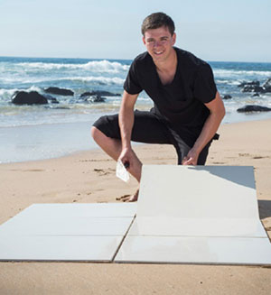 Photo of Luke Wray demonstrating tile laying at the beach