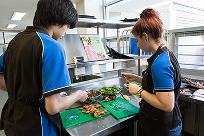 Photo of college hospitality students preparing healthy meal menu in college kitchens