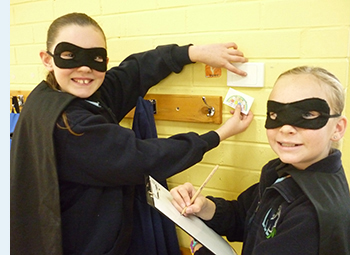 Photo of two female primary students, dressed as Power Rangers, monitoring energy use at their school