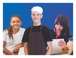 Picture of 3 high school students one looking at a laptop, one with a chef hat on and one sitting on a chair