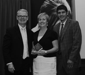 Photo of Gai Beecher Principal of Gungahlin College receiving an award from Microsoft Partners in Learning for Schools Pilot Program along with two other dignitaries.