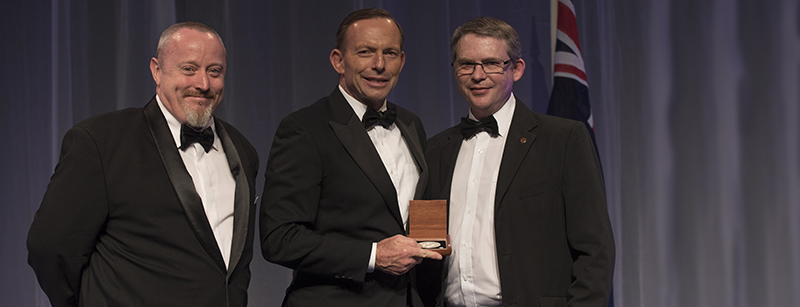 Photo of Mr Geoff McNamara (right) receiving his award from Prime Minister, the Hon Tony Abbott MP, for Excellence in Science Teaching in Secondary Schools with Mr Simon Vaughan, Principal, Melrose High School