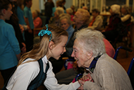 Photo of primary student welcoming older member of community as guest of school event