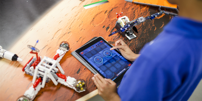 Photo of primary school student constructing and operating spacecraft from Lego materials and electronic device