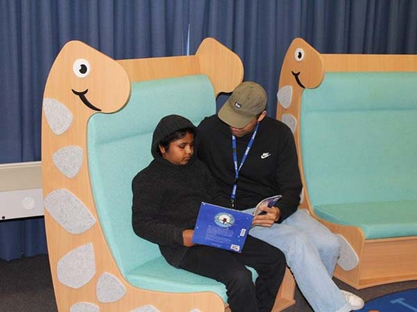 Two people are reading a book on a dinosaur seat