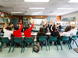 Photo of students raising their hands to answer their teacher