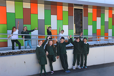 Photo of primary students photographed against graphic wall component of new classrooms at Duffy Primary