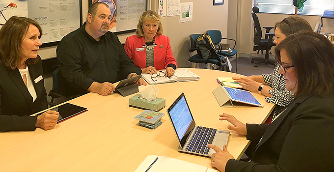 Photo of five school executives from different high schools, planning curriculum collaboration for their schools