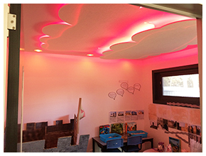 Classroom space with ceiling details of clouds backlit with red light.