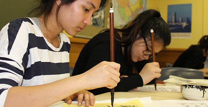 Photo taken at the launch of the Mandarin Blueprint, showing two girls writing with calligraphy pens.