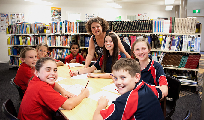 Photo of seven students and their teacher, working together at a desk in the school library