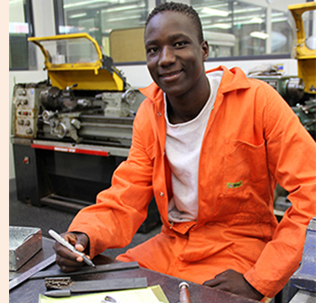Photo of a male college student in the automotive workshop.