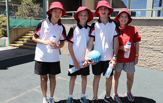 Photo of four primary students in sports attire, with hats and drink bottles