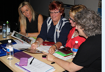 Photo of four female school executives collaborating during an activity, as part of the Principals as Literacy Leaders (PALLs) program