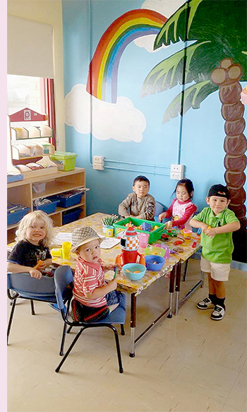 Photo of five preschool children, seated around a table, doing craft activities