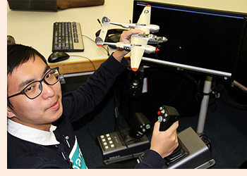 Photo of a male college student with a remote-controlled aircraft