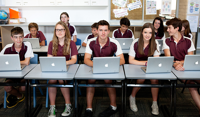 Photo of a high school classroom, with the students seated at their desks, working on laptops