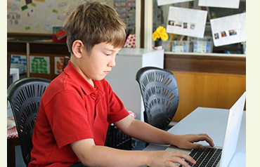 Photo of a primary boy, working on a laptop at his desk