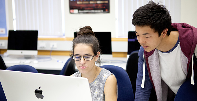 Photo of two college students, a boy and a girl, working together at a laptop computer