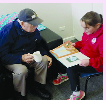 Photo of an elderly gentleman, who is a volunteer at the Community Hub, listening to a child read