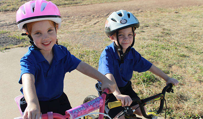Photo of a primary boy and girl, wearing bike helmets, seated on their bicycles