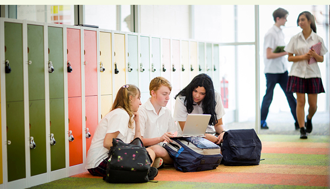Photo of three high school students, 2 girls and a boy, seated in the locker bay, working on a laptop