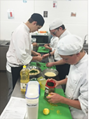 Four hospitality students preparing food in a commercial kitchen at a school