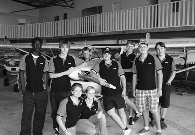 Photo of ten college age students involved in new career options. They are in an aeroplane mechanic workshop standing in front of aircraft.