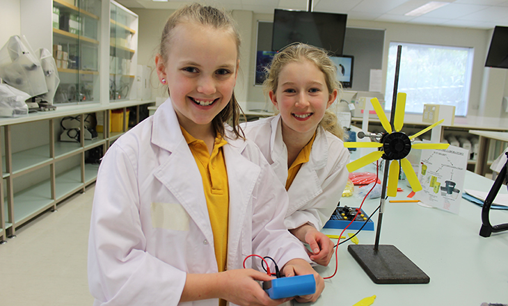 Photo of two high school girls in lab coats working with science equipment