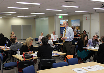 Photo of a presenter delivering a workshop to college and high school executives during the Principals as Literacy Leaders (PALLs) program