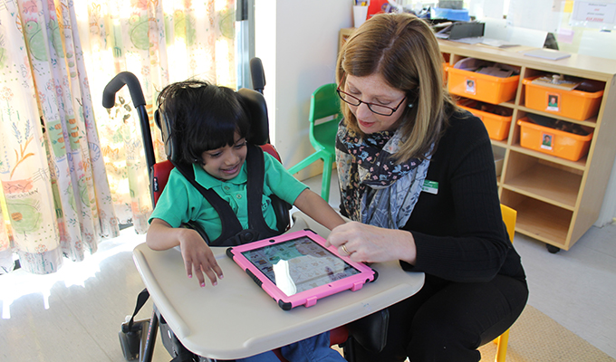 Photo of a teacher assisting a disability student to use an iPad.