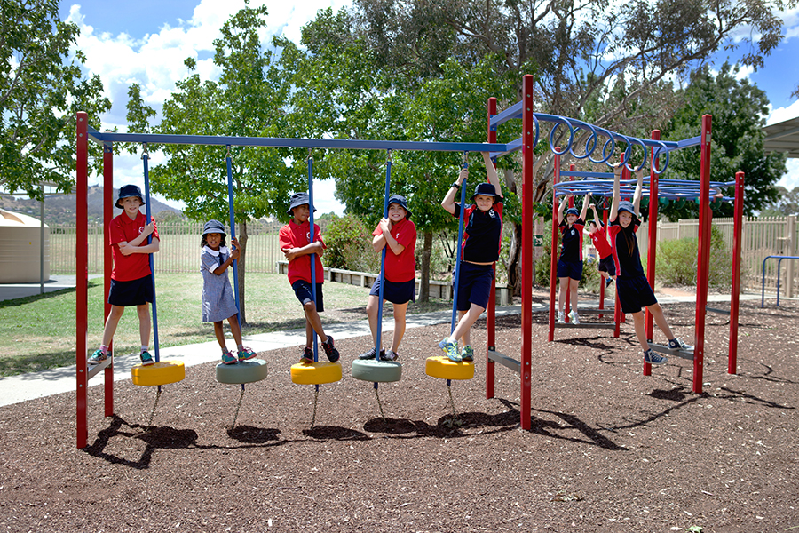 Photo of a group of primary school students playing on equipment in Gilmore Primary School playground