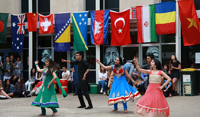 Photo of a group of five college students in their national costume, performing a traditional dance on United Nations Day