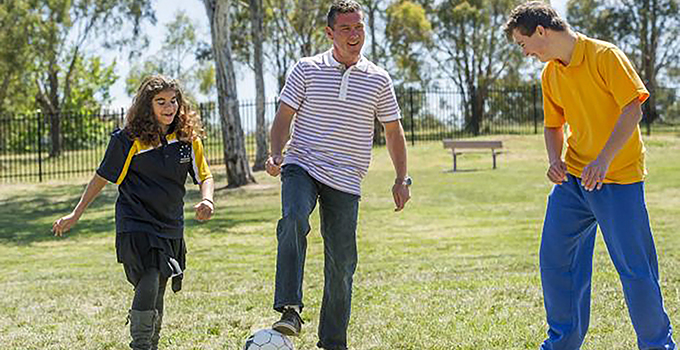 Photo of award winning teacher Jarrod McGrath, playing soccer with a male and female student
