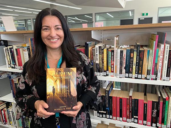 Gungahlin College teacher and Aurealis Awards shortlisted novella author Angela Rega with the recently published anthology Aurum. (Photo: Brenton Sloane)